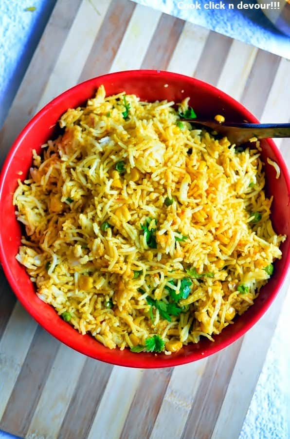 Overhead shot of peas corn pulao srved in a red bowl