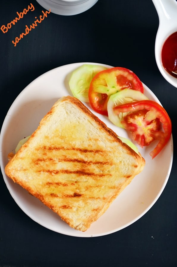 Grilled Bombay Veg Sandwich served in a white plate with cucumber and tomato rings for breakfast