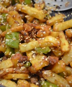 honey sesame chilli potatoes-add potatoes and coat with sesame seeds