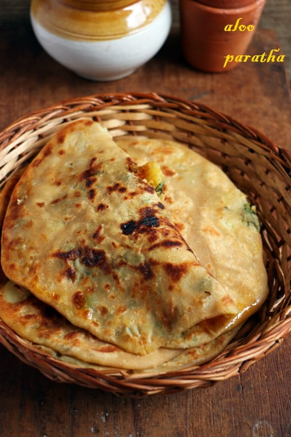 Aloo paratha served on a bamboo plate with pickle and yogurt for breakfast!