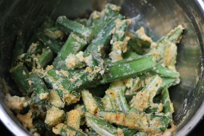 Making Kurkuri Bhindi Recipe- mixing okra with flours