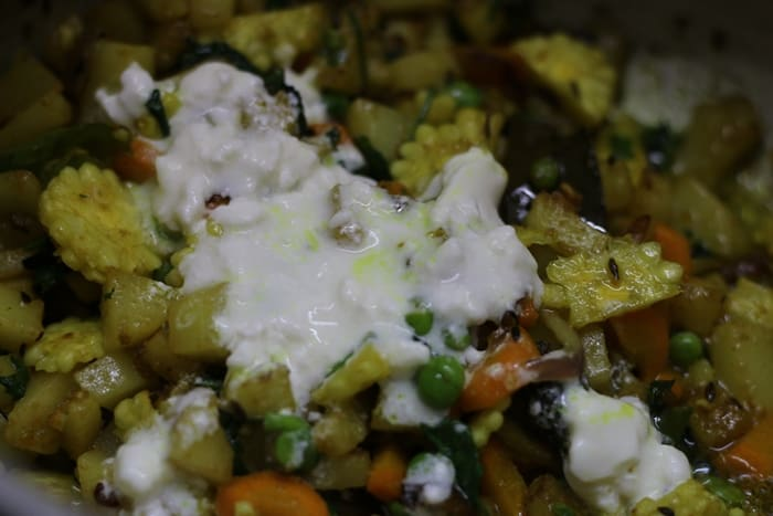 Adding curd to veggies for making veg tahiri recipe