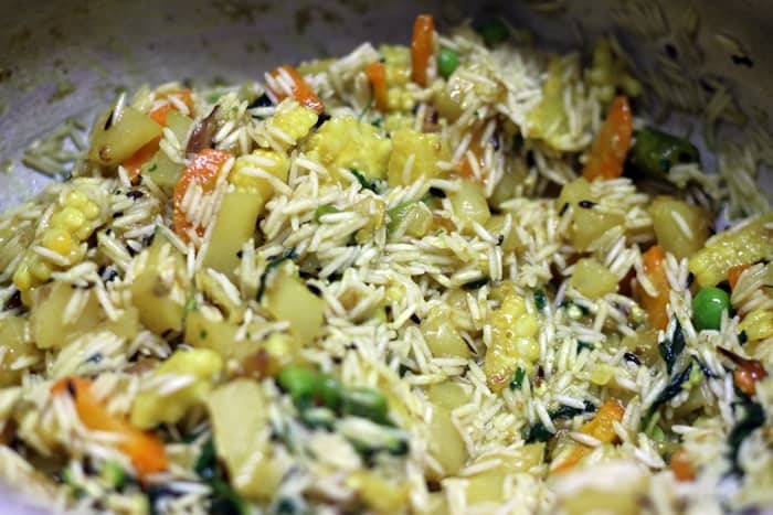 Adding basmati rice to sauteed veggies for making veg tahiri recipe