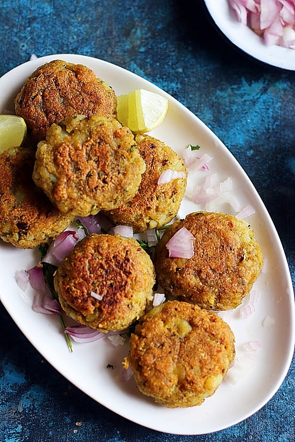 Crispy street style aloo tikki served in a ceramic plate topped with finely chopped raw onions and lemon wedges