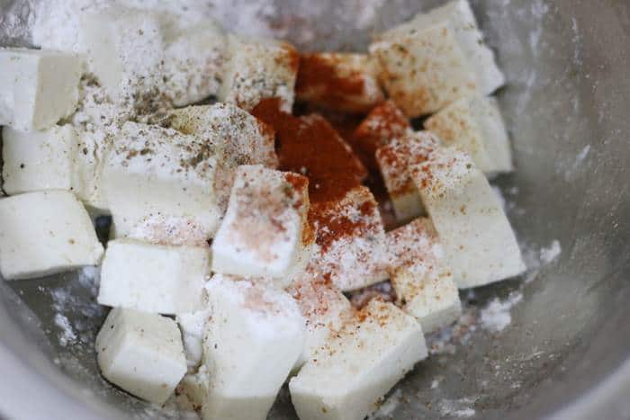 paneer cubes, red chili powder, pepper powder and salt placed in a mixing bowl.