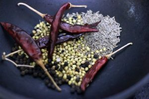 roasting whole spices -coriander seeds, dry red chilies, cumin seeds and black peppercorns for kadai masala
