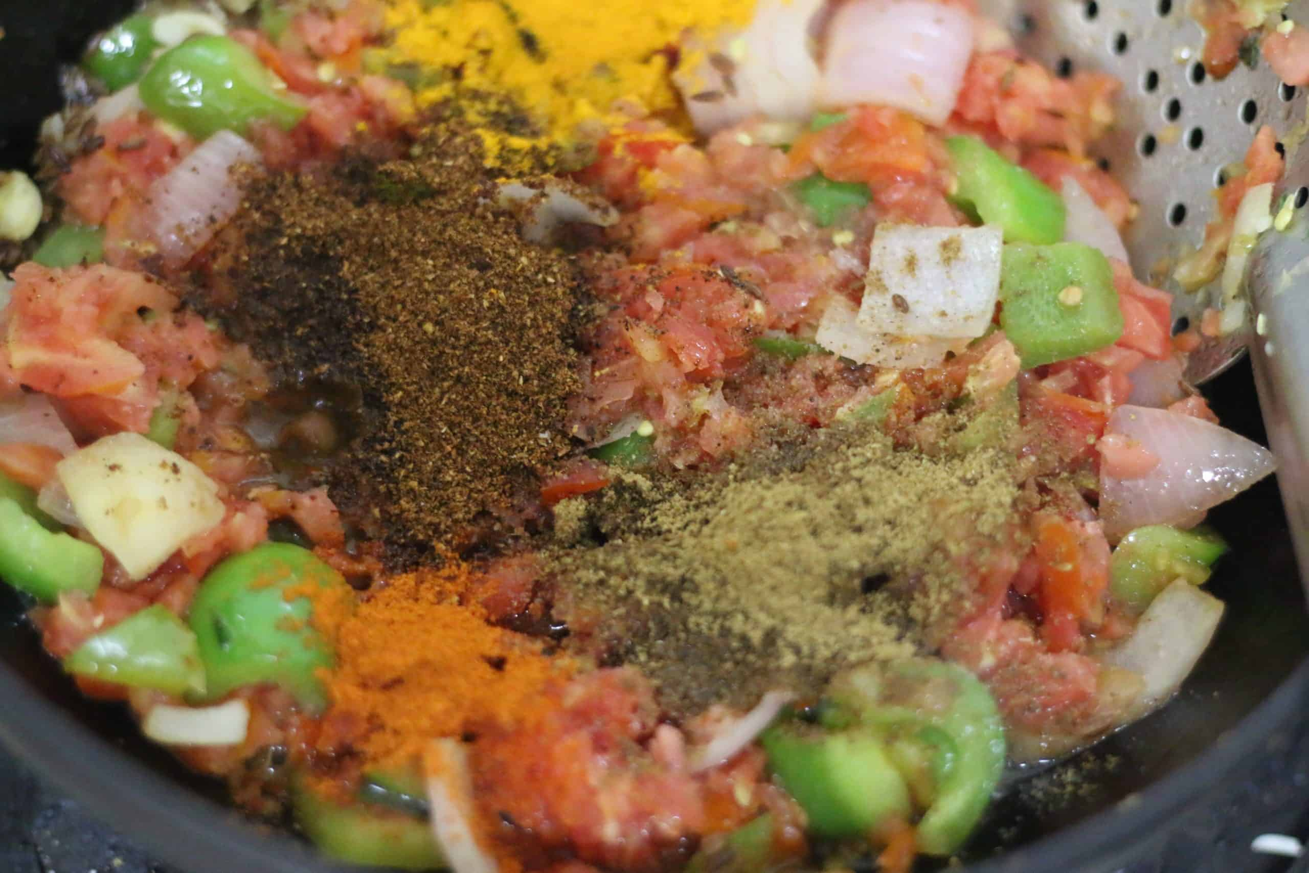 kadai masala, garam masala added to onion tomato base for kadai paneer recipe