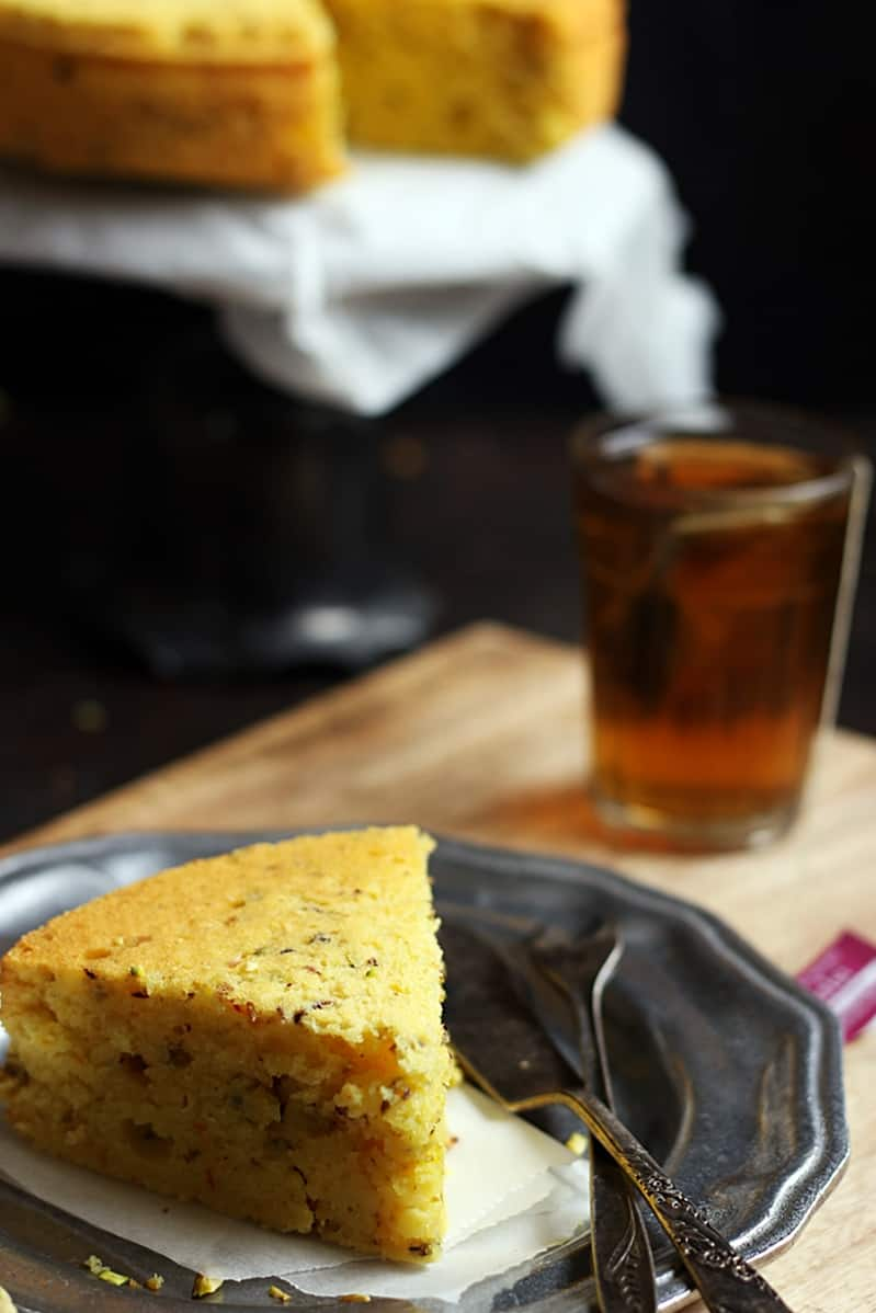 A slice of Iranian mawa cake with tea, more cake in background