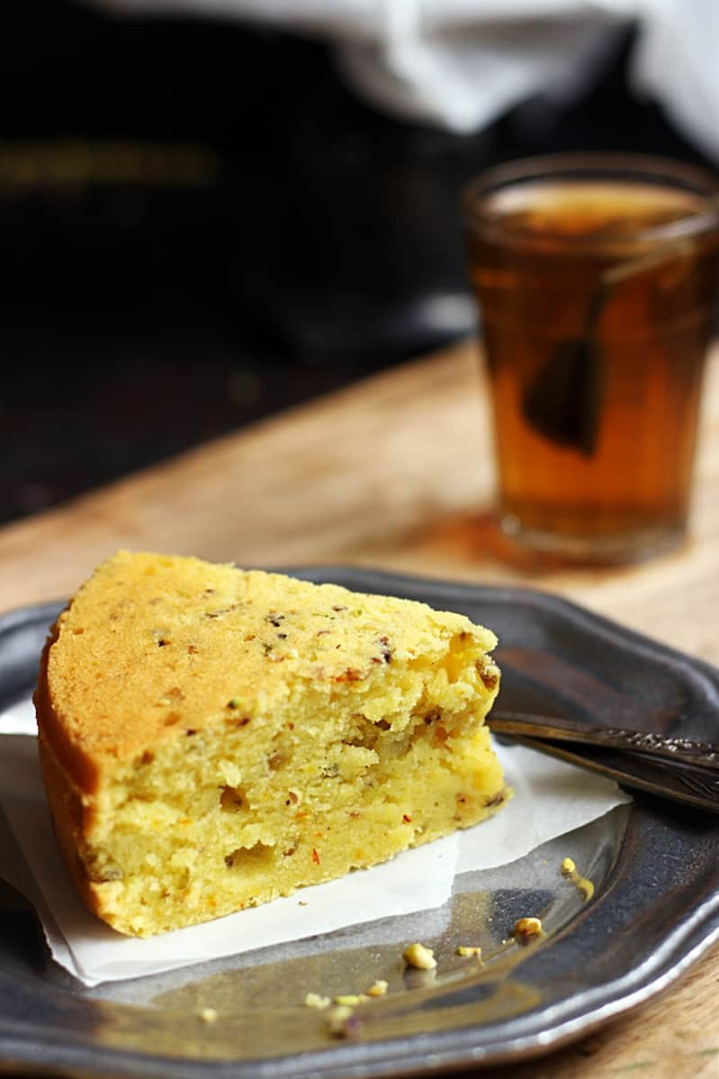 A slice of eggless mawa cake served in a metal plate with black tea
