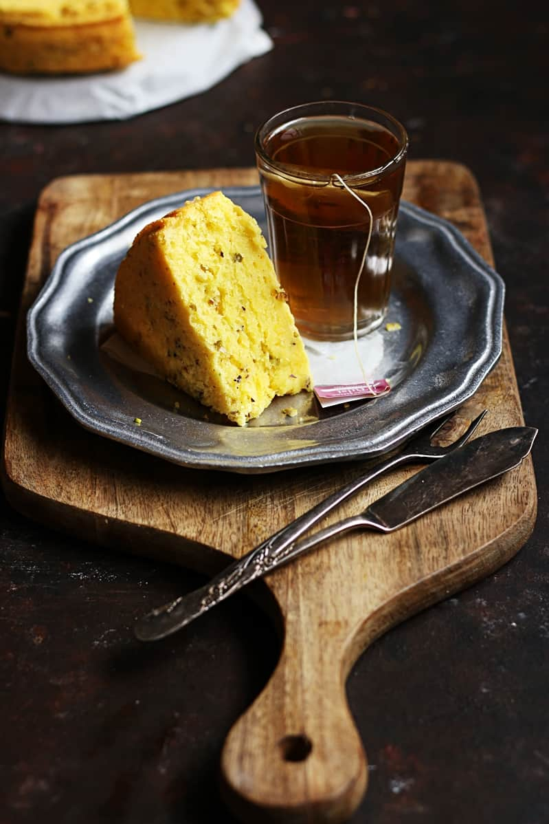 eggless mawa cake sliced and served with tea on a serving board