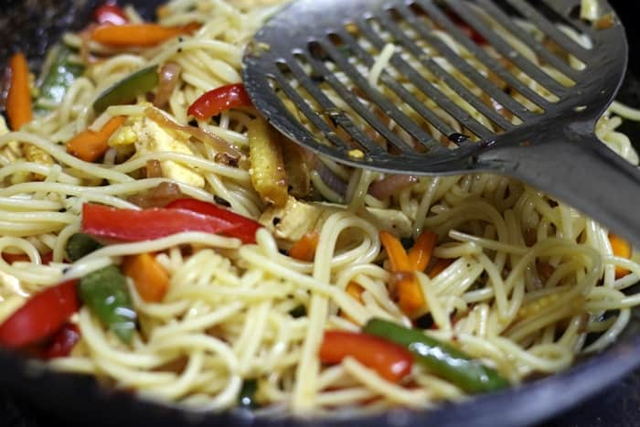 tossing noodles in veggies for making chilli garlic noodles