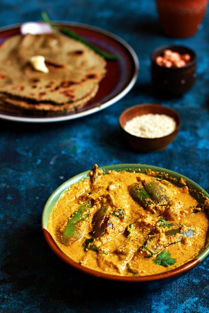 Tasty bharli vangi- Indian eggplant curry served in a two toned bowl with rotis and butter.