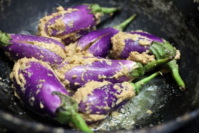 Sauteing stuffed eggplants for making bharli vangi recipe
