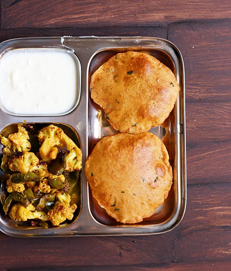 Overhead shot of aloo puri served with cauliflower and curd in a segmented plate.