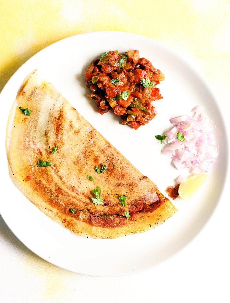 overhead shot of crispy paper thin pav bhaji dosa with side dish and chopped onions