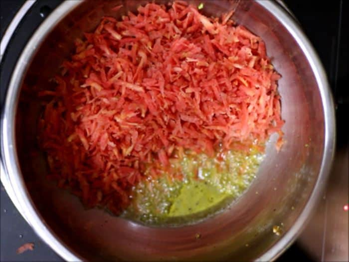 sauteing grated carrots in ghee for gajar halwa recipe