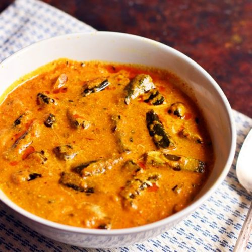 Dahi bhindi recipe- tangy and mildly spiced okra in yogurt curry served for lunch in a white serving bowl.