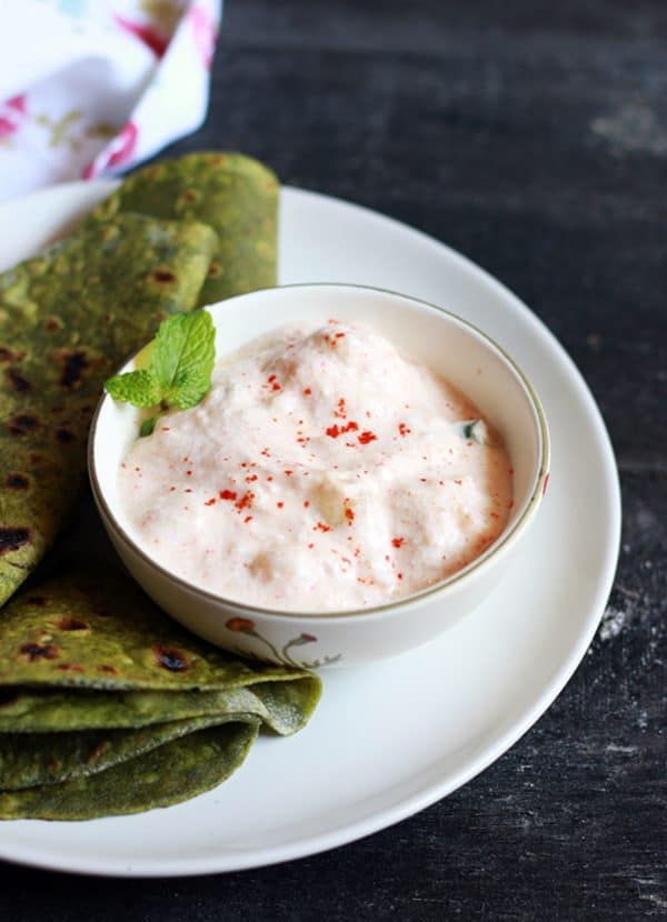 Aloo raita garnished with mint leaves served in a small bowl as side dish for palak paratha