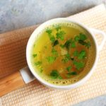 Quick and tasty lemon rasam garnished with cilantro leaves and served on a white soup bowl.