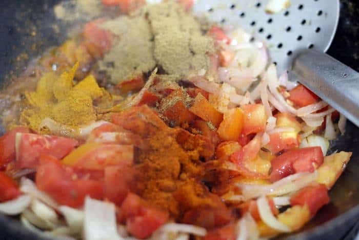 spice powders added to sauteed tomatoes