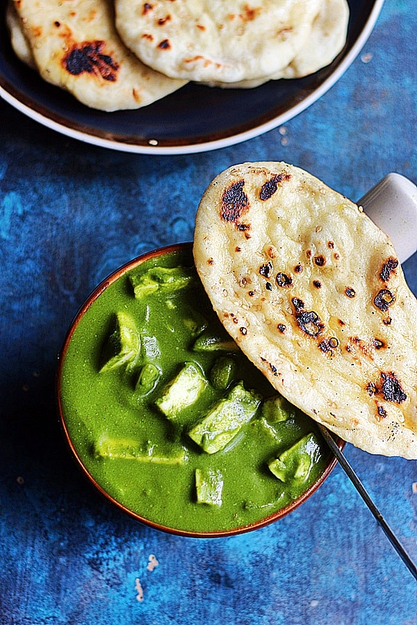 palak paneer served in a bowl with naan on top and a spoon.