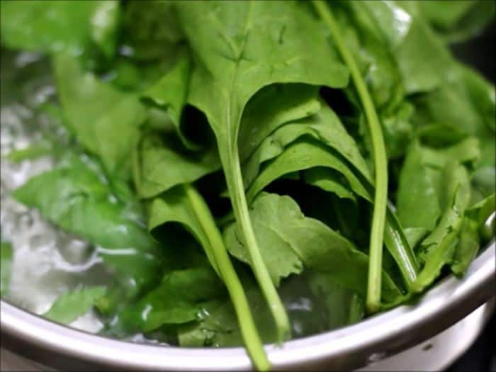 blanching spinach leaves in boiling water.