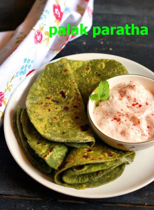 palak paratha recipe- healthy and tasty palak paratha or spinach paratha served on a white snack plate with raita/yogurt