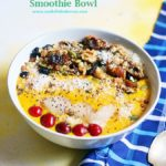 Mango smoothie bowl with assorted toppings served with a spoon