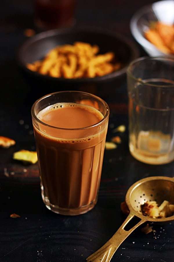 A strong cup of ginger tea or adrak chai served with savory snacks