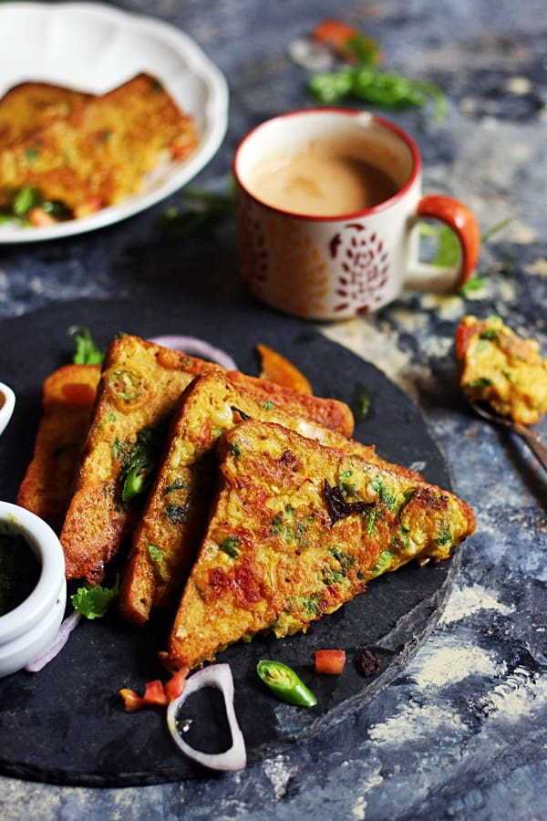 A stack of vegan savory french toasts on a black tray served with coffee for breakfast