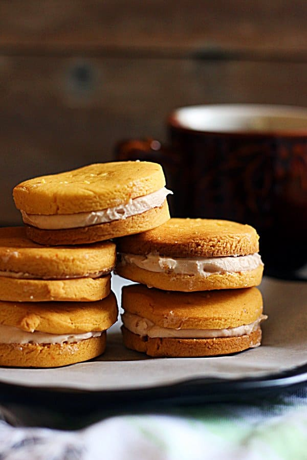 rose flavored custard creams stacked in a plate with coffee in the background