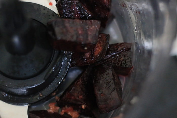 pulsing roasted beets in a food processor