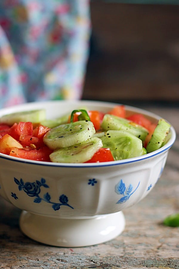 Closeup shot of easy summer tomato cucumber salad served in a footed blue and white bowl