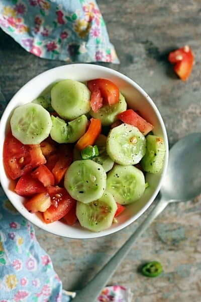 overhead shot of fresh cucumber tomato salad with lemon dressing served in a white and blue bowl.