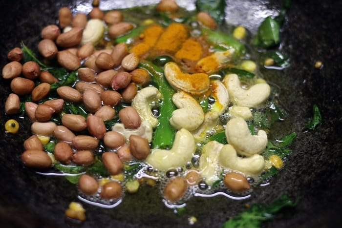 Frying peanuts, cashews and turmeric powder in oil