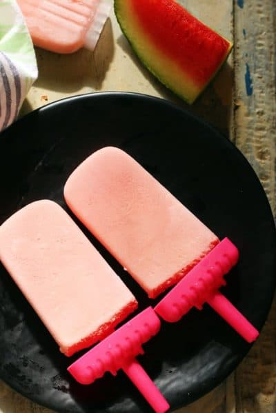 creamy watermelon popsicles served on ablack plate for dessert