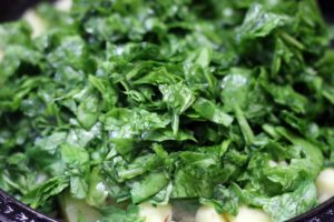 Finely chopped spinach leaves added to sautéed potatoes