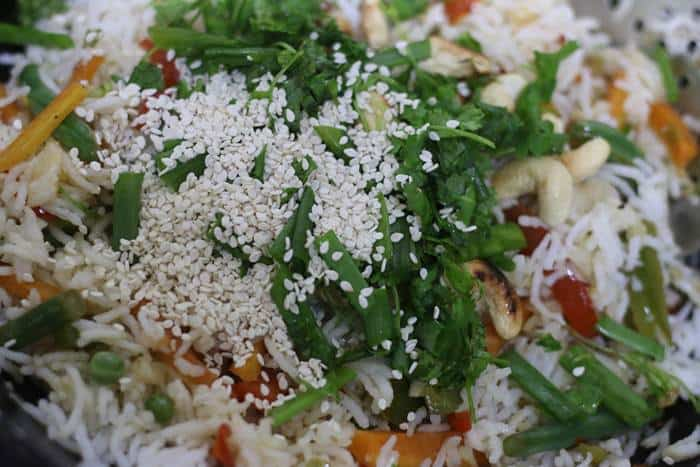 basil leaves cilantro leaves, cashews and sesame seeds added as topping for fried rice