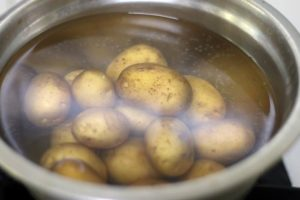 boiling tiny potatoes in hot water with salt.