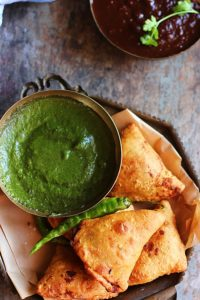 crispy samosa- vegetable samosa in a copper plate with green chutney