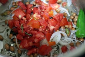 sautéing tomatoes in oil along with onions
