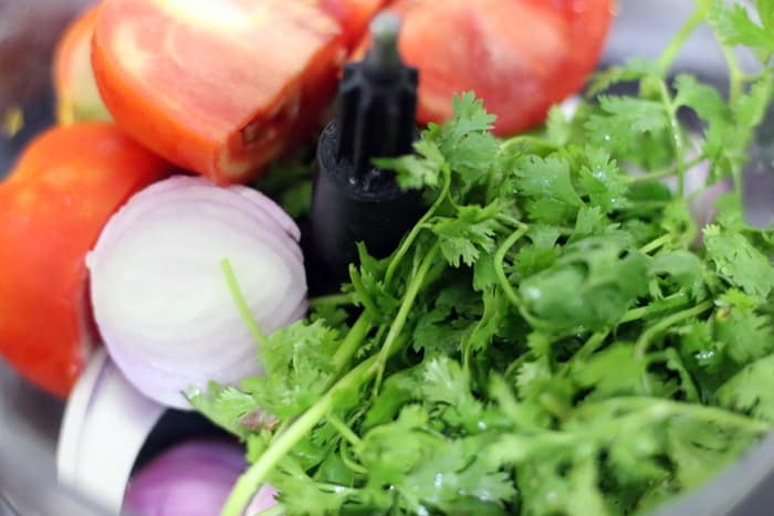 onions, tomatoes, green chiles and coriander leaves in a food processor jar