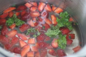 sliced berries and mint leaves added to water
