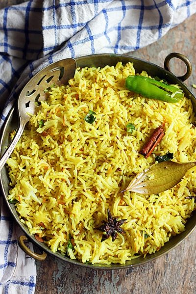 easy turmeric rice recipe in a copper bowl with a spoon