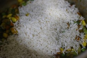 rice added to cooked vegetables for curried rice recipe